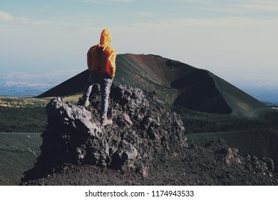 male hiker looking at recent volcanic crater in Etna Park, Sicily