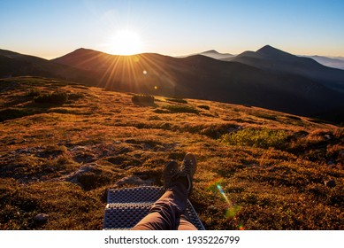 Male hiker lying on grass on top of mountain and looking at amazing sunset. Close up of male legs. Relaxation and adventure concept.