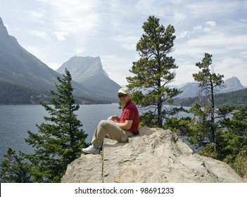 A male hiker rests on a large boulder while enjoying a healthy snack by a beautiful mountain lake.