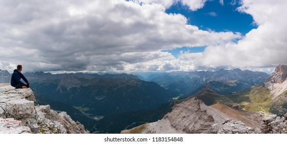 male hiker sitting on a mountain peak ledge in the Dolomites and looking at the amazing view of the surrounding landscape with Langkofel and Marmolada peaks