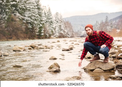 Male hiker sitting on the stone and testing water in the river