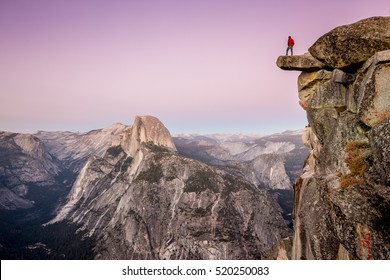 A male hiker standing on an overhanging rock at Glacier Point enjoying the breathtaking view towards famous Half Dome in beautiful twilight after sunset in summer, Yosemite National Park, California