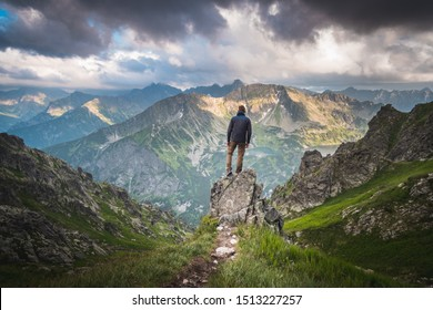 Male hiker standing on a rock above deep valley in front of scenic panorama of high mountains with dark clouds above him.