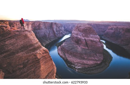 A male hiker is standing on steep cliffs enjoying the beautiful view of Colorado river flowing at famous Horseshoe Bend overlook in beautiful post sunset twilight on a summer evening, Arizona, USA