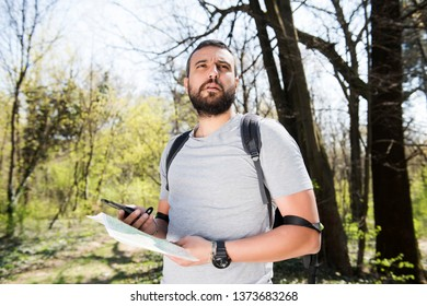 Male hiker using a map to locate the destination