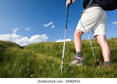 Male hiker walking along a mountain path. Horizontal orientation. Low angle view