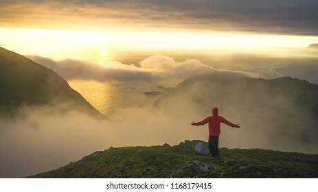 Male hiker walking on top of mountain looking at beauty morning landscape. Man hiking silhouette. Midnight sun on Lofoten islands in Norway during summer polar day