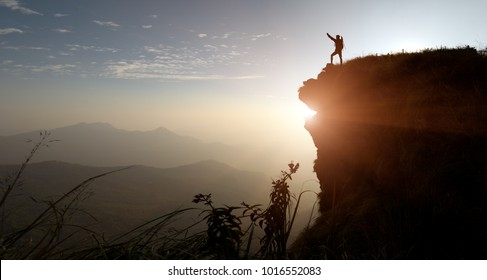 Male hikers climbing up silhouette mountain cliff .Together we can, teamwork ,success ,helps , Business Leadership concept .