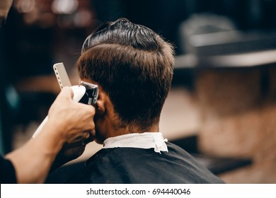 Male hipster in barbershop barber on fashionable haircut, rear view. Toned photo.