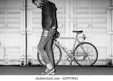 Male hipster on fixed-gear bicycle at night. Black and white portrait