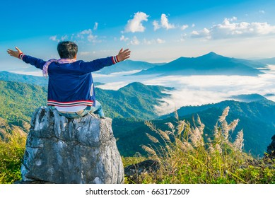 Male Hipster Traveler sit on the stone with beautiful mountain landscape background, adventure, travel, tourist concept