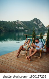 Male and his girlfriend sitting in deck chairs near lake and eating burgers