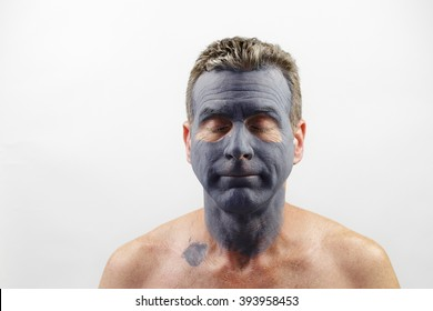 Male in his late forties wearing a charcoal and bentonite clay face mask beauty treatment. Front portrait of a white male wearing a bentonite mud mask beauty treatment.