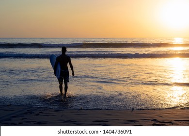 A male with his surfboard under his arm is entering the water to surf during the sunset in Nosara, Costa Rica