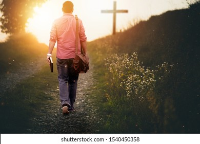 A male holding the bible walking up to the hill towards the cross with a blurred background