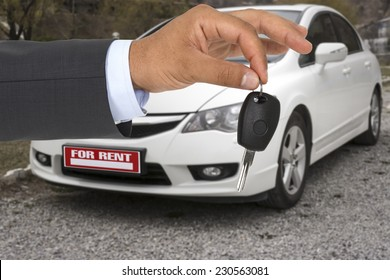Male holding car keys with a rental car on background