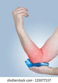 Male holding ice gel pack on elbow. Medical concept photo.  Color Enhanced skin with read spot indicating location of the pain.