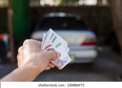Male holding money with car on background