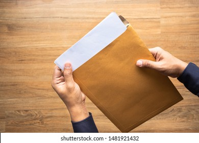 Male holding paper envelope, letter on floor wood. business concepts ideas