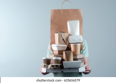 Male holding pizza box, take-out food containers, coffee cups in holder and paper bag, close-up. Light grey background, place to insert your text. Delivery man.