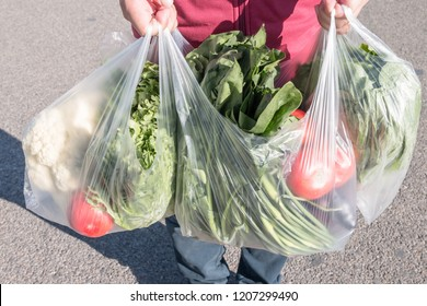 Male holding a plastic bag of vegetables