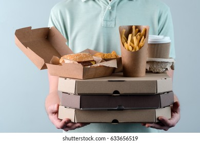 Male holding several pizzas, hamburger in paper food container, take-out coffee cups in holder and French fries, close-up. Light grey background. Fast food delivery.