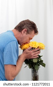 Male holding and smelling a bunch of yellow roses. Bouquet of yellow roses being held and smelled. Dozen yellow roses arrangement with tiny pink streaks held by a man who is appreciating their scent.
