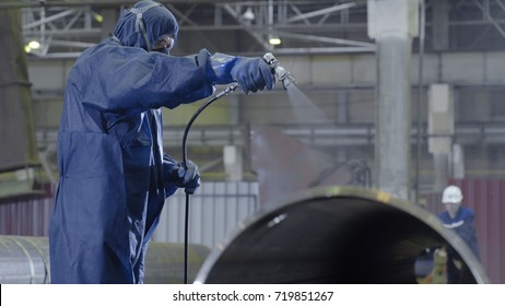 Male holding spray gun and painted steel. Man paints pipe atomizer