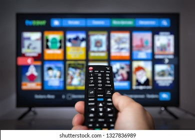Male holding TV remote control in front of TV