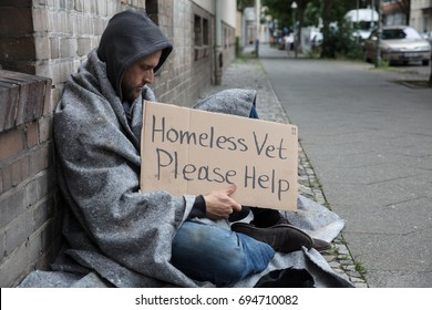 Male Homeless Sitting On A Street With Sign Asking For Help In City