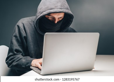 Male hooded hacker with hidden face accessing to personal information on laptop in the dark. Technologal, cyber crime concept.