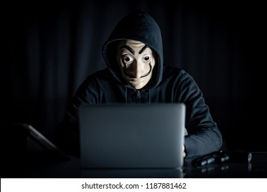 Male hoodie hacker wearing mystery mask using laptop computer sitting with digital tablet and gun on the table. Anonymous social masking. Ransomware cyber attack or internet security concepts