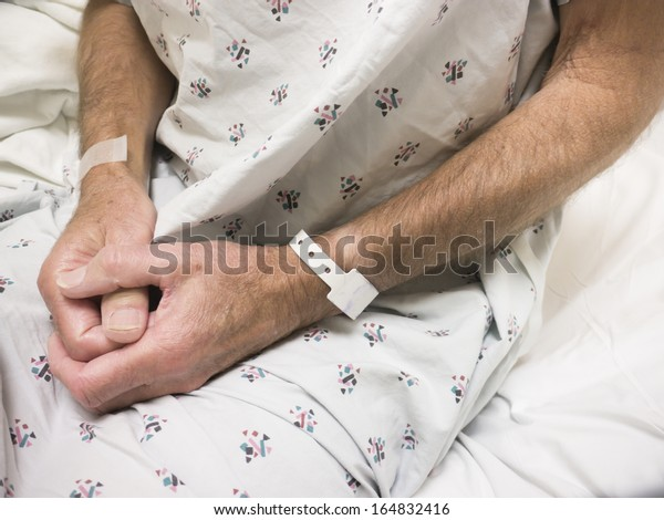 Male hospital patient wearing gown and ID bracelet