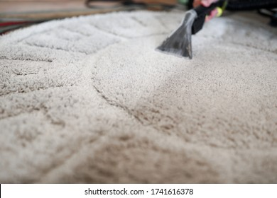 Male housekeeper arm cleaning carpet with washing vacuum cleaner closeup. Professional house wash business concept