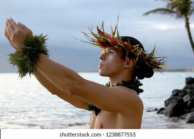 Male Hula Dancer performs on the beach in Hawaii with expressive hand movements