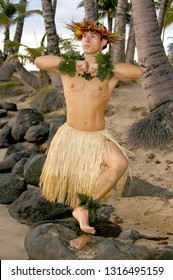 A male hula dancer poses in front of palm trees on the beach in Hawaii.