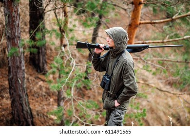 male hunter with binoculars ready to hunt, holding gun and walking in forest. hunting and people concept