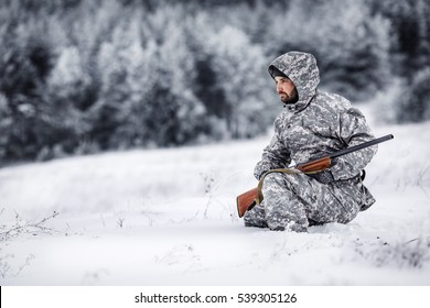 Male hunter in camouflage, armed with a rifle, sitting  in a snowy winter forest