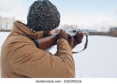 male hunter with gun on a cold winter day. back view close up photo. copy space