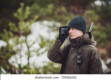 male hunter ready to hunt, holding laser finder in forest. hunting and people concept