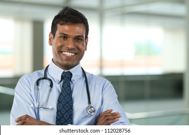 Male Indian General Practitioner or GP standing in hospital with background out of focus.
