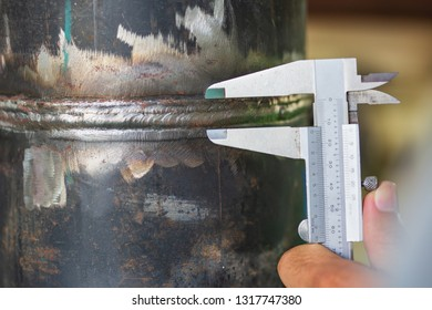 Male industrial engineer visual inspection weld joints pipe using vernier calipers