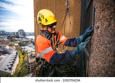 Male industry rope access technician job wearing orange helmet using plastic glove abseiling working on concrete repair at construction building site near the rock, in Sydney city CBD, Australia