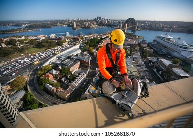 Male industry rope access using twin rope wearing helmet working and abseiling, off on construction building high rise site, back ground is Sydney harbour bridge in Sydney city CBD, Australia