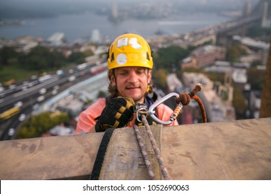 Male industry rope access wearing helmet using twin ropes, safety back up device working, abseiling, off on construction in high rise building site near the rock in Sydney city CBD, Australia