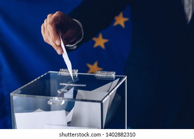 Male inserting his vote to ballot box. European Union elections
