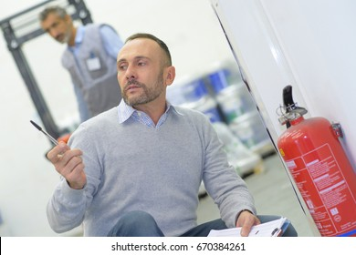 male inspector checking fire extinguisher in office