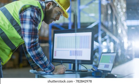 Male Inspector Fills up Spreadsheets on His Personal Computer. He's in Big Warehouse with Rows of Pallet Racks.