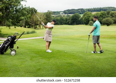 Male instructor assisting woman in learning golf at golf course