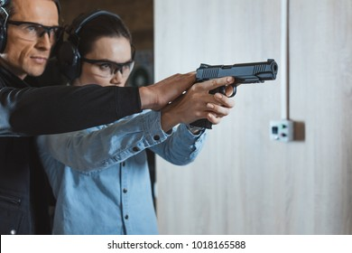 male instructor helping customer to shoot with gun in shooting range